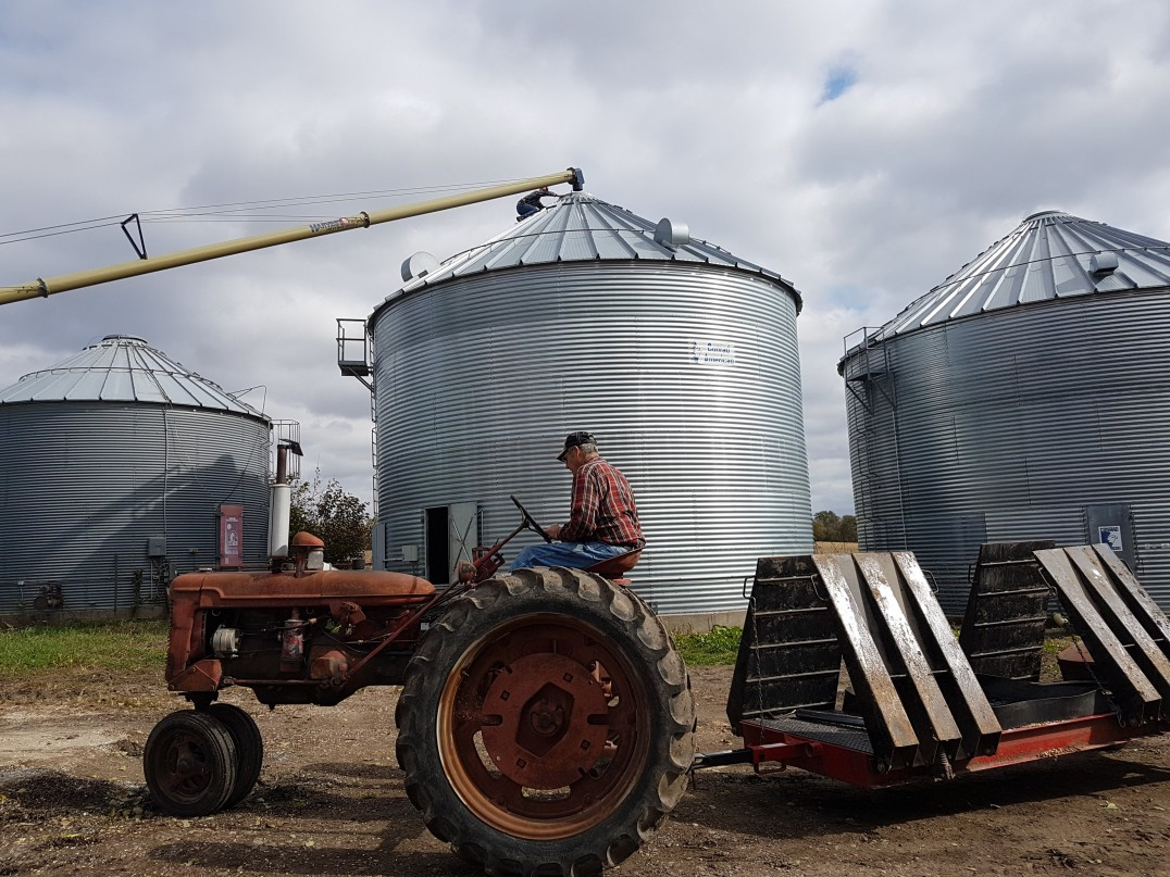 Wade's Dad driving tractor and grain bins